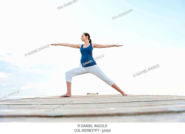 Pregnant woman on pier in yoga position, Majorca, Spain