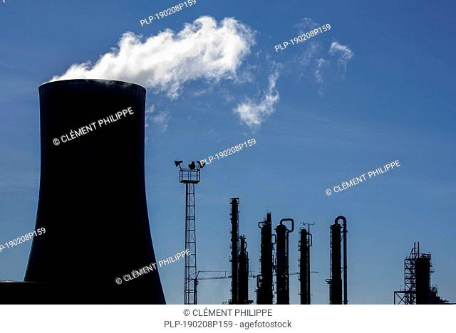 Silhouette of industrial estate showing cooling tower of the BASF chemical production site in the port of Antwerp, Belgium