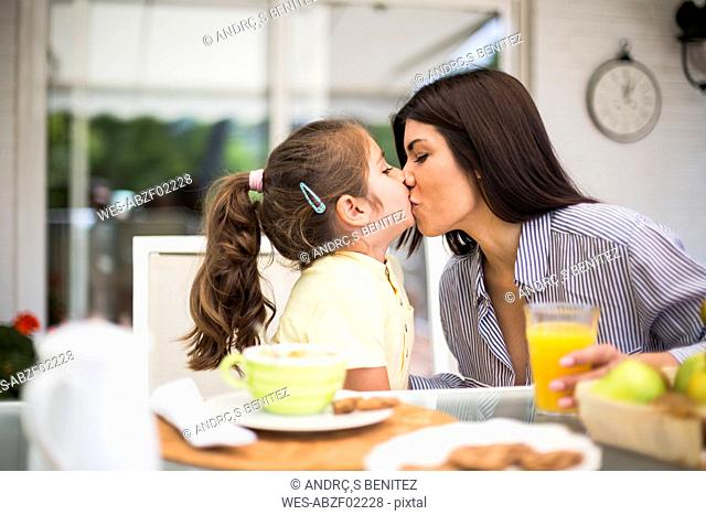 Mother and daughter kissing during breakfast at home
