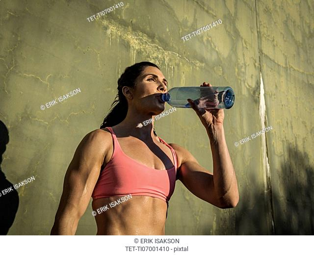 Woman drinking water during exercise break