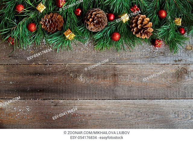 Christmas card on wooden background with snow fir tree, pine cones and decorative baubles. View with copy space