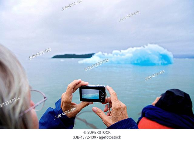 A sightseeing senior woman with a digital camera photographs ice from Le Conte Glacier, the southernmost tidewater glacier in the United States, near Petersburg
