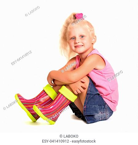 Seated cute little blond girl in a blouse, a skirt and rubber boots isolated on white background