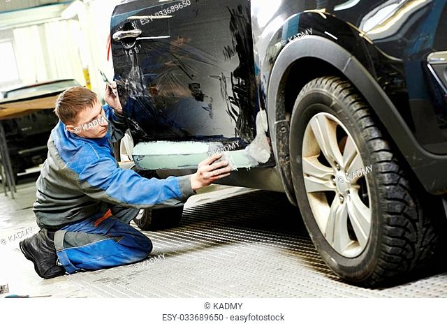 repairman worker in automotive industry stopping car body before painting or repaint at auto repair shop