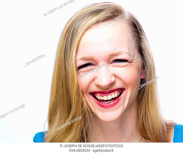 A happy 25 year old blond woman smiling at the camera with squinting eyes