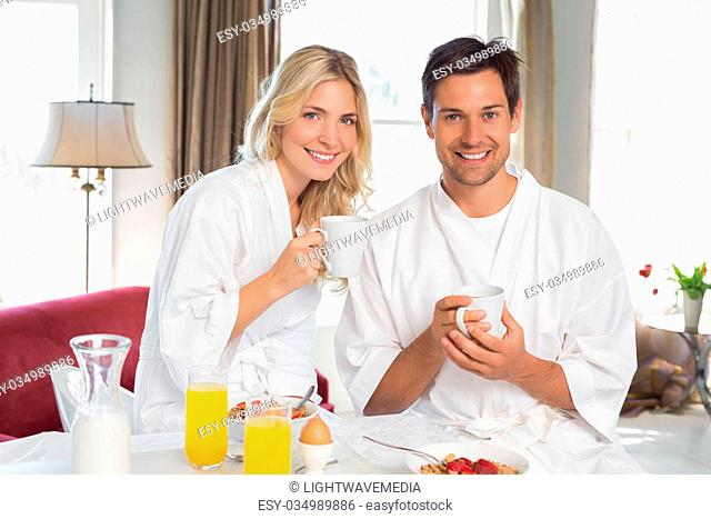 Portrait of a happy young couple having breakfast at home