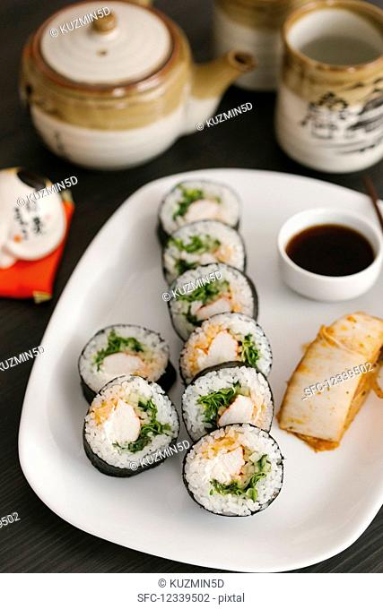 Maki sushi with soy sauce on a serving plate