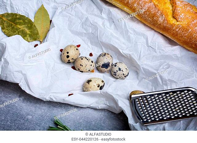 A view from above on a set of lunch ingredients on a white grease-proof paper background. White baguette, quail eggs, bay leaves, and metal grater