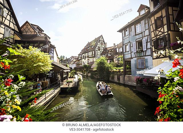 Tourists boat along channel at Little Venice in medieval town of Colmar, Alsace (department of Haut-Rhin, region of Grand Est, France)