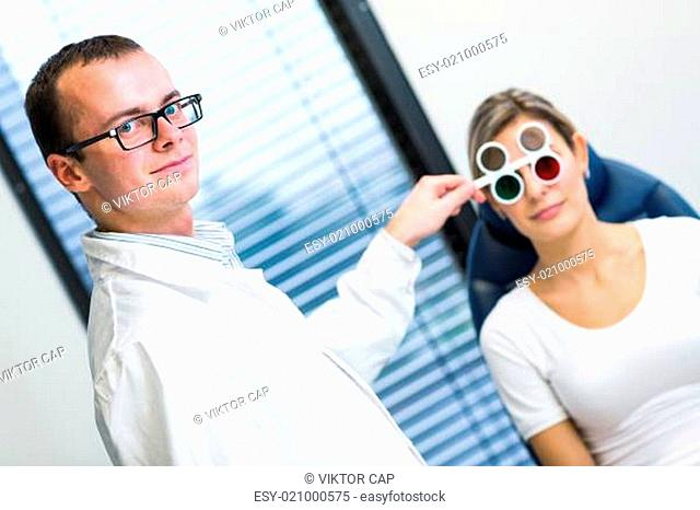 Optometry concept - pretty young woman having her eyes examined by an eye doctor/optometrist
