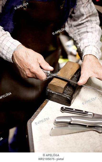 Cropped image of man sharpening knife on block in workshop