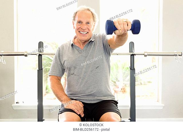 Caucasian man sitting on bench lifting dumbbell
