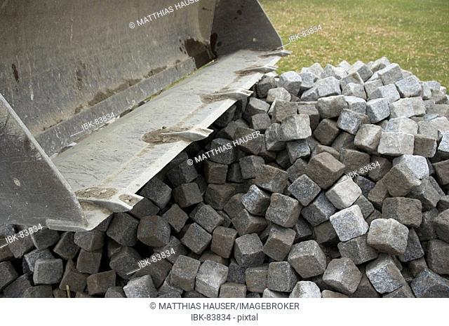 Construction site: excavator shovel with cobblestones