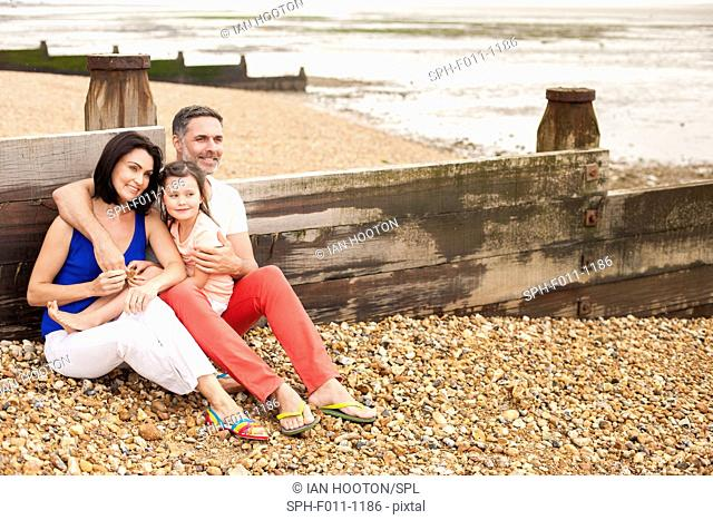 Parents sitting on the beach with their daughter