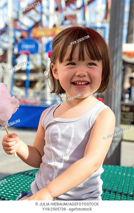 Three year old girl eating cotton candy at the amusement park, San Diego, California