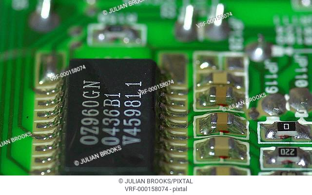 track past an electronic circuit board, green, extreme close up