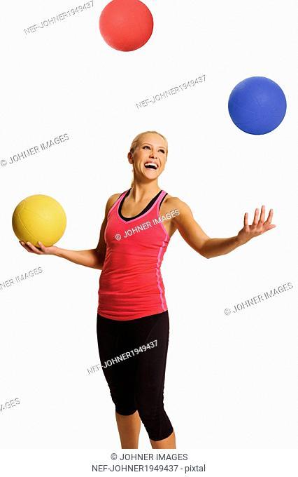 Woman juggling balls, studio shot