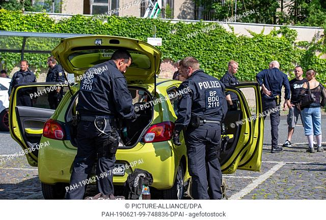 21 June 2019, Saxony, Ostritz: Police search a vehicle in the parking lot opposite the hotel where the so-called Sword and Shield Festival takes place
