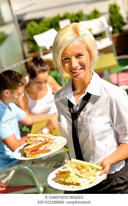 Waitress bringing sandwiches on plates fresh lunch