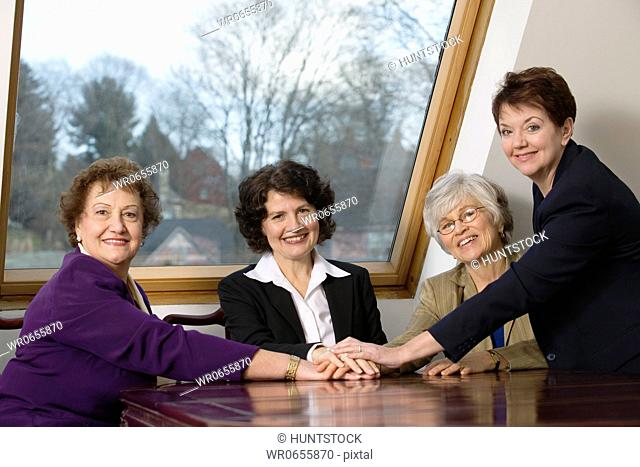 Portrait of smiling business women sitting at table