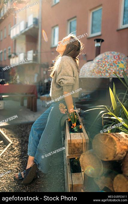 Young woman relaxing in garden in sunshine