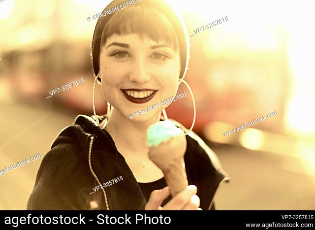 woman with ice cream during sunny winter day in city Cottbus, Brandenburg, Germany