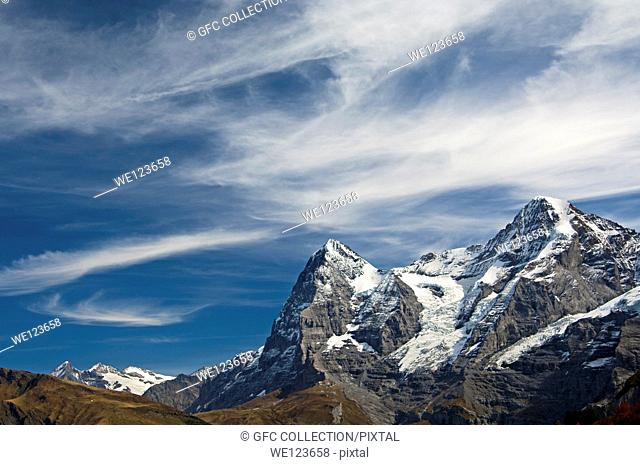 The mountain range of the Bernese Alps with the Eiger summit under a dramatic sky with cirrus clouds, Bernese Oberland, Switzerland