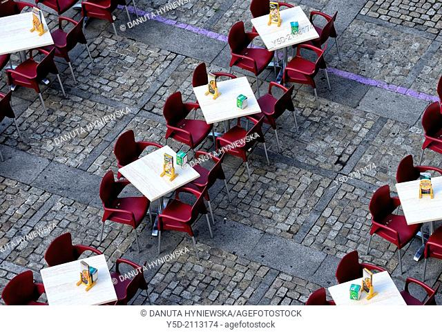 empty outside restaurant tables and chairs seen from above, paved Cathedral square, Cadiz, Andalusia, Spain