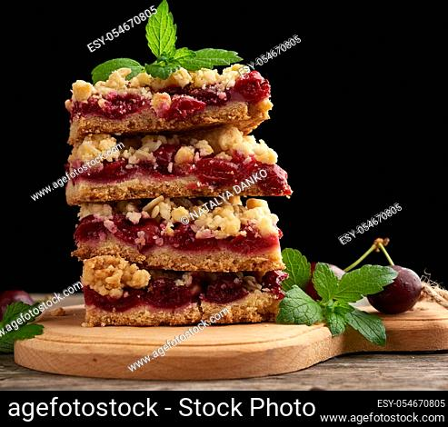 stack of square slices of a pie with red cherry, black background, delicious crumble