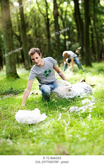 Young man picking up trash in nature