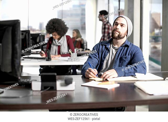 Man with pencil at desk in office thinking