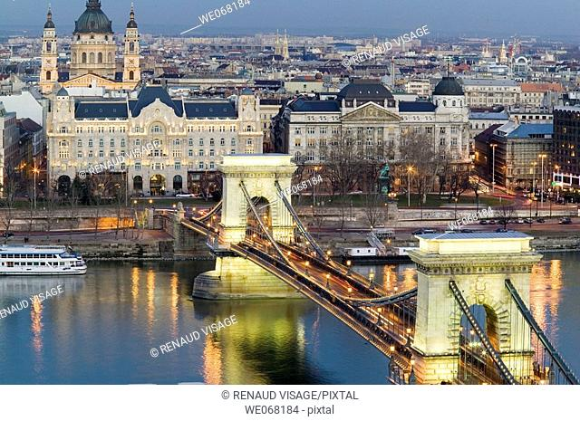 Szechenyi Chain Bridge over the Danube lit up at night viewed from Castle Hill with St Stephen Basilica in the background. Budapest. Hungary