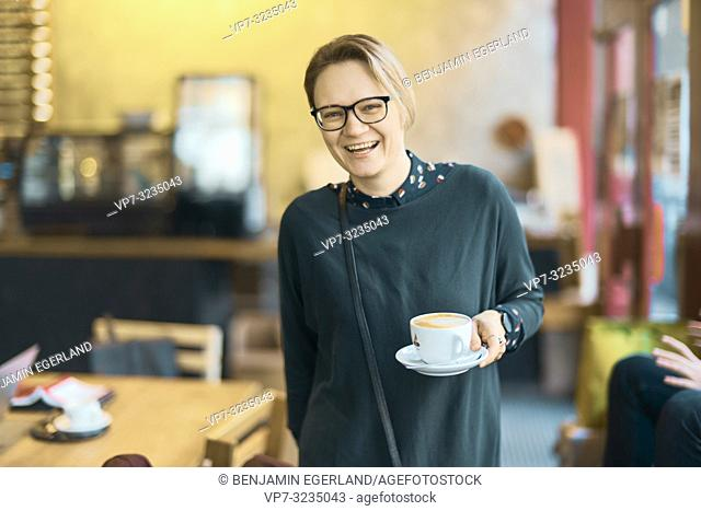 laughing woman holding coffee cup indoors in café, happy, in Munich, Germany