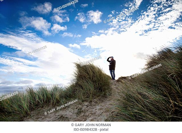 Woman on dune shielding eyes looking away