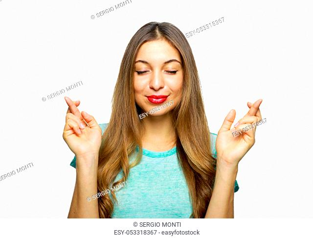 Positive and charming girl wearing azure t-shirt expressing excitement while making with or hoping for something with raised hands and crossed fingers