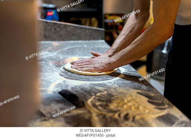 Close-up of pizza baker preparing pizza dough in kitchen