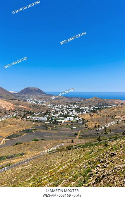 Spain, Canary Islands, Lanzarote, Maguez, Village Haria and Volcano Monte Corona in the background