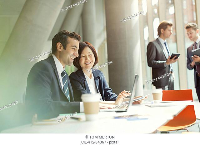 Businessman and businesswoman meeting working at laptop in conference room