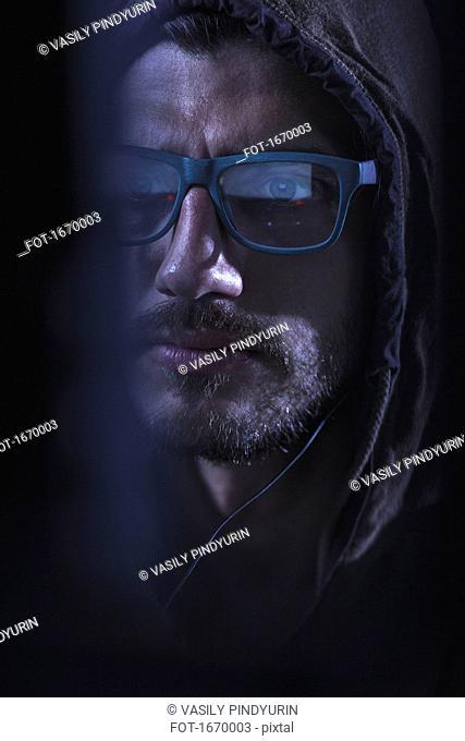 Close-up of serious man wearing eyeglasses and hood