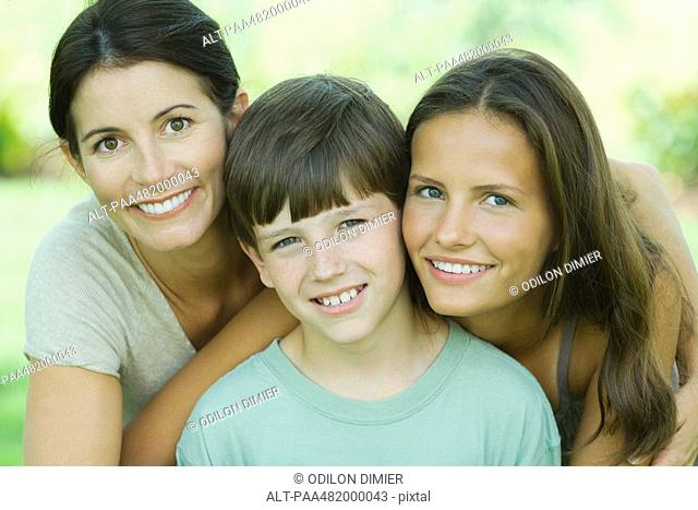 Mother with teenage daughter and son, all smiling at camera, portrait