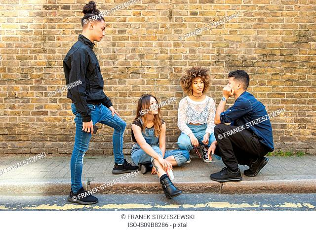 Four friends hanging out in street, talking