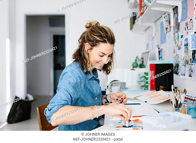 Young woman painting with watercolour
