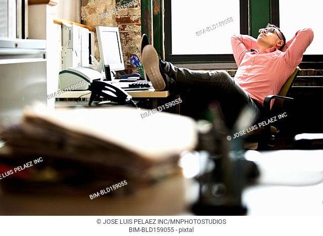 Hispanic businessman relaxing at office desk