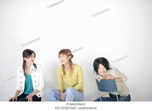 Young women by white wall