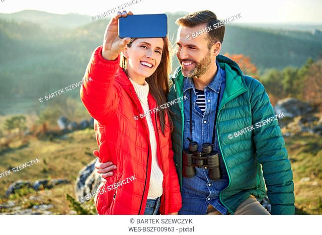Happy couple on a hiking trip in the mountains taking a selfie