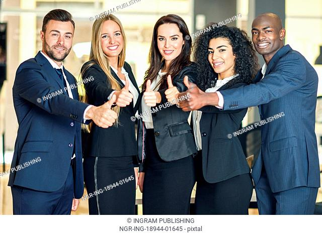 Group of businesspeople with thumbs up gesture in modern office. Multi-ethnic people working together. Teamwork concept
