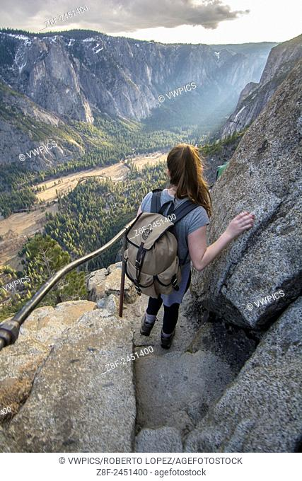 A young woman hiking down to Yosemite Point with an amazing view of the Valley of Yosemite, California, USA