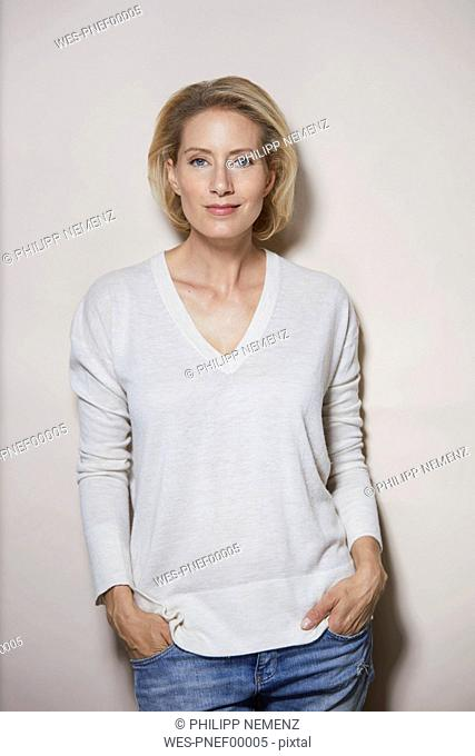 Portrait of smiling blond woman in front of light background