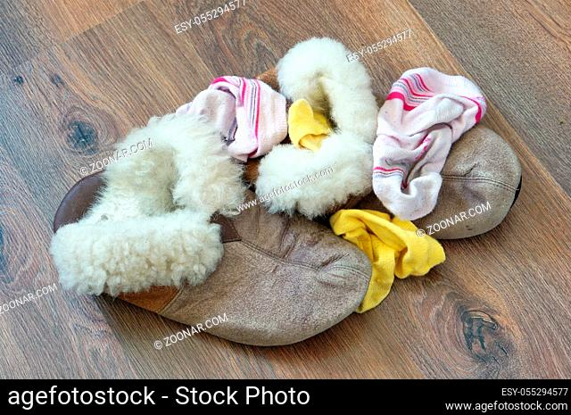 Old fur women's house slippers and socks lie a bunch on the wooden floor