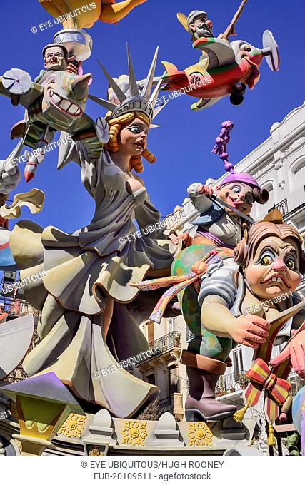 Papier Mache figure of a woman resembling the Statue of Liberty with various other figures flying around her during Las Fallas festival